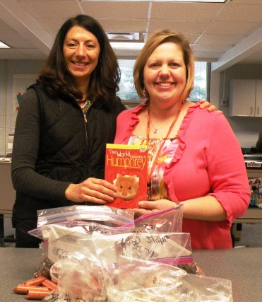 Ms. Amanda Sanders (left) and Ms. Karen Shrader (right) with the donated coins, currency, and checks.
